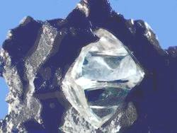 Misshapen octahedral rough diamond crystal in matrix